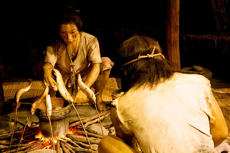 縄文時代の狩猟で捕獲した獲物を食べる